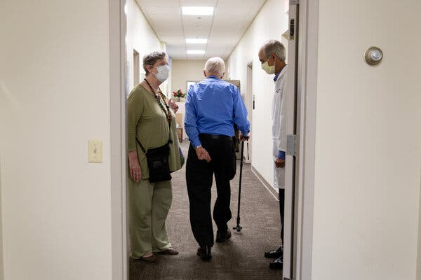 Henry Magendantz, center, a participant in the clinical trial of the experimental Alzheimer's drug, aducanumab, with his wife, Kathy Jellison, and Dr. Stephen Salloway, leaving the hospital after receiving an infusion.